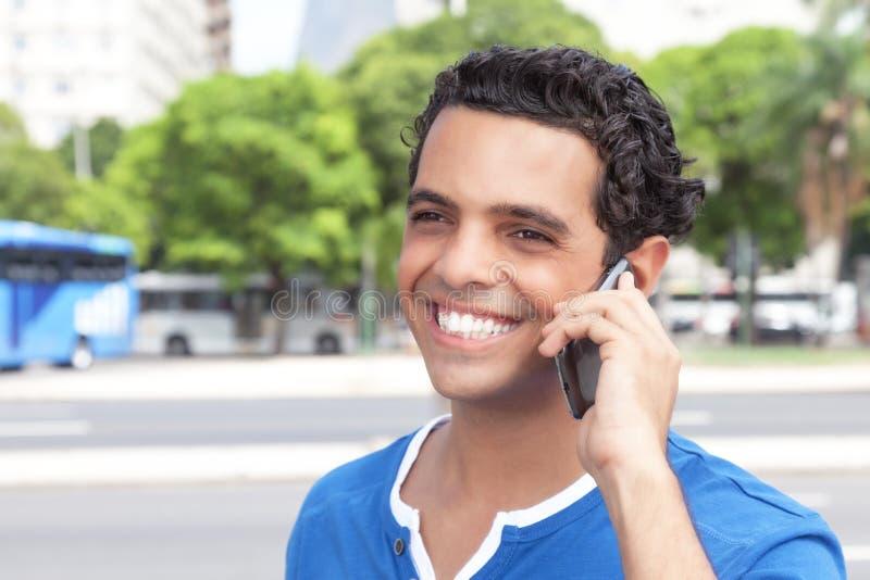 Roześmiany łaciński facet z telefonem komórkowym w mieście zdjęcie stock