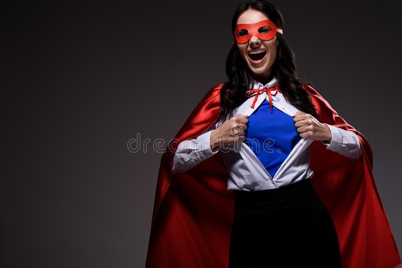 roześmiany atrakcyjny super bizneswoman w czerwonym przylądku i maska pokazuje błękitną koszula obraz royalty free
