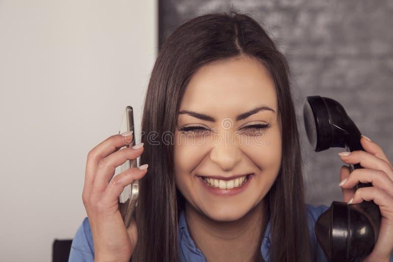 Roześmiany bizneswoman prowadzi rozmowy nad dwa telefonami fotografia stock
