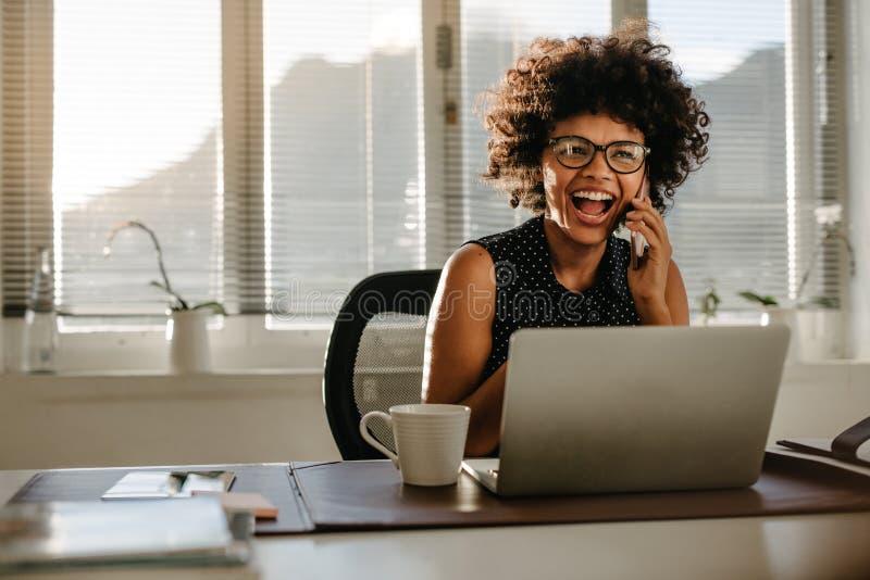 Roześmiany bizneswomanu obsiadanie przy jej pracy biurkiem zdjęcie royalty free