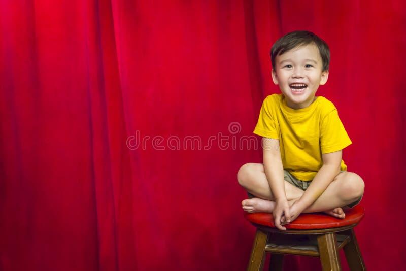 Roześmiany chłopiec obsiadanie na stolec przed zasłoną zdjęcie royalty free