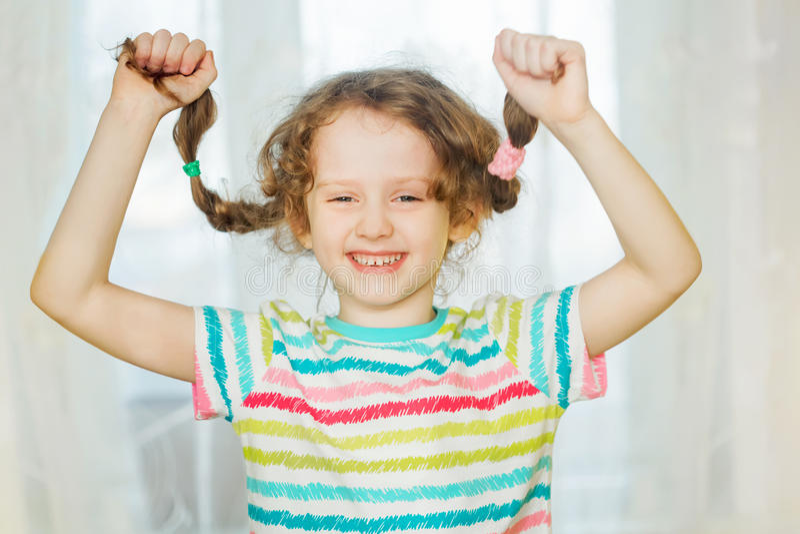 Roześmiany dziewczyny ciągnienie jej pigtails up ręką i pokazuje ona ząbkuje fotografia royalty free