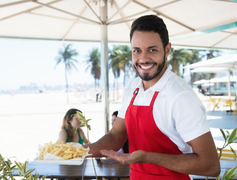 Roześmiany kelner porci francuz smaży przy plaża barem obrazy royalty free