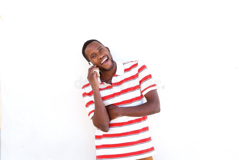 Roześmiany młody afrykański mężczyzna opowiada na telefonie komórkowym fotografia royalty free