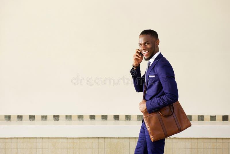 Roześmiany młody biznesowego mężczyzna odprowadzenie i opowiadać na telefonie komórkowym zdjęcia stock