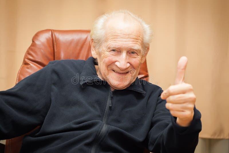 Roześmiany stary człowiek z aprobatami zdjęcie royalty free
