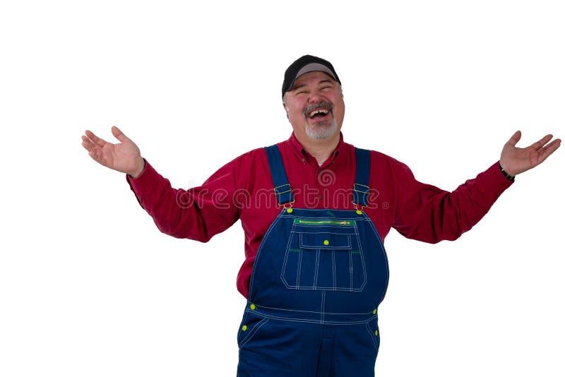 Roześmiany szczęśliwy mężczyzna podnosi jego w dungarees ręki zdjęcie stock