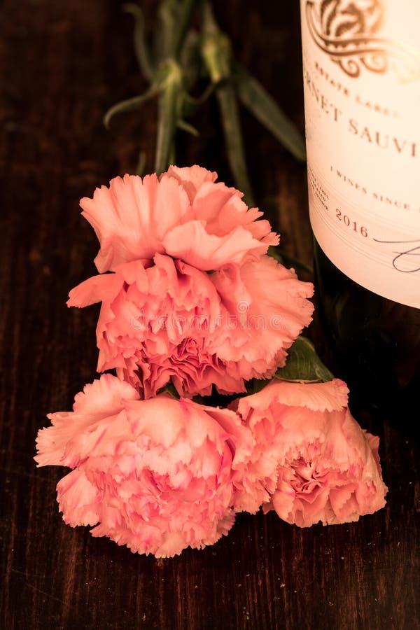 Roze Anjers en een Fles Rode Wijn stock foto's