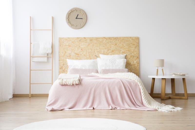 Roze bedsheets op kingsize bed stock foto
