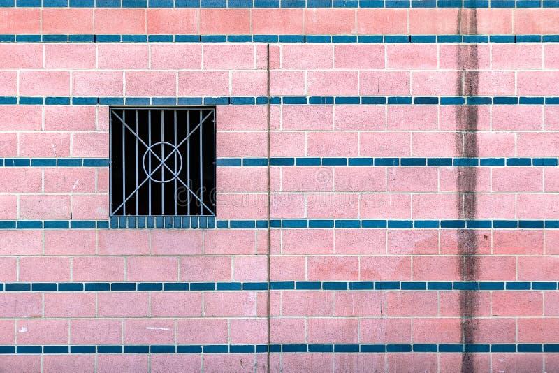 Roze betegelde muur met vuile watervlekken en een metaal versperde windo royalty-vrije stock fotografie