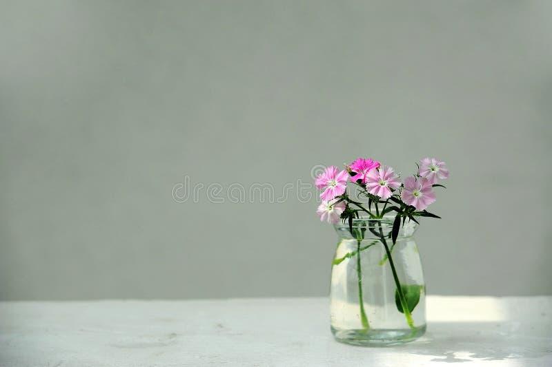 Roze bloemen in een glasfles royalty-vrije stock afbeelding