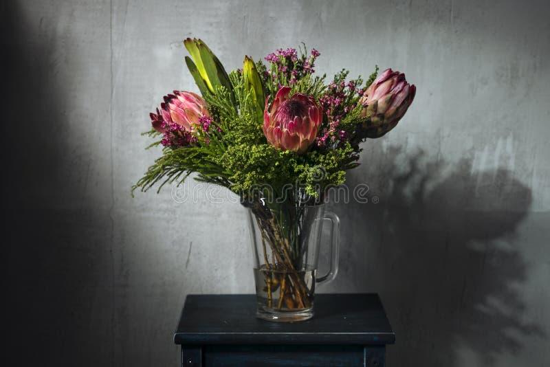 Roze bloemen in fles in zolderbinnenland royalty-vrije stock foto