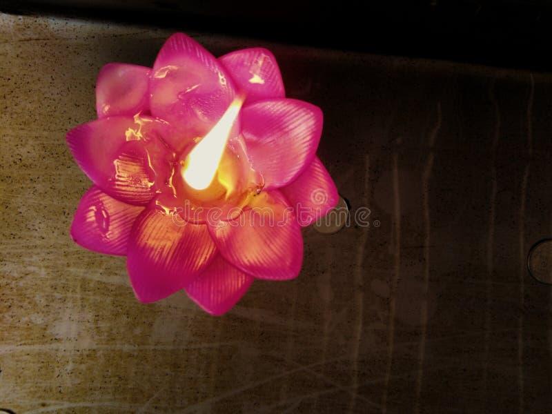 Roze bloemkaars met een drijvende vlam stock foto