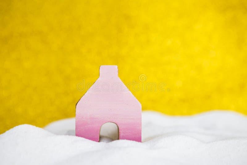 Roze blokhuis op witte sneeuw over vage gouden achtergrond royalty-vrije stock fotografie