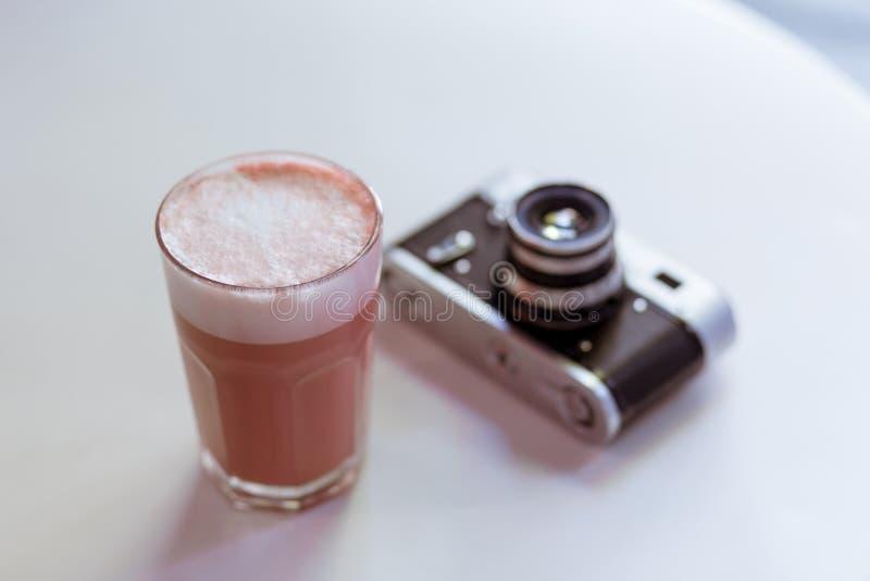 Roze cappucciono van de hipsterkoffie op de witte lijst met ouderwetse retro de fotocamera van de stijlfilm royalty-vrije stock foto
