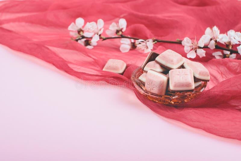 Roze chocoladereep en witte bloem op roze en rode achtergrond Robijnrode nieuwe chocolade Nieuw roze zoet dessert royalty-vrije stock afbeelding