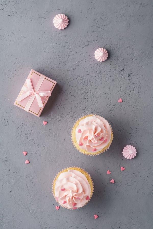 Roze cupcakes, giftdoos en suikergoed Creatieve dessertachtergrond royalty-vrije stock afbeelding