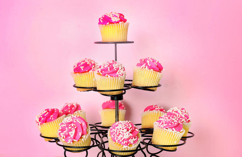 Roze cupcakes op roze achtergrond royalty-vrije stock afbeeldingen