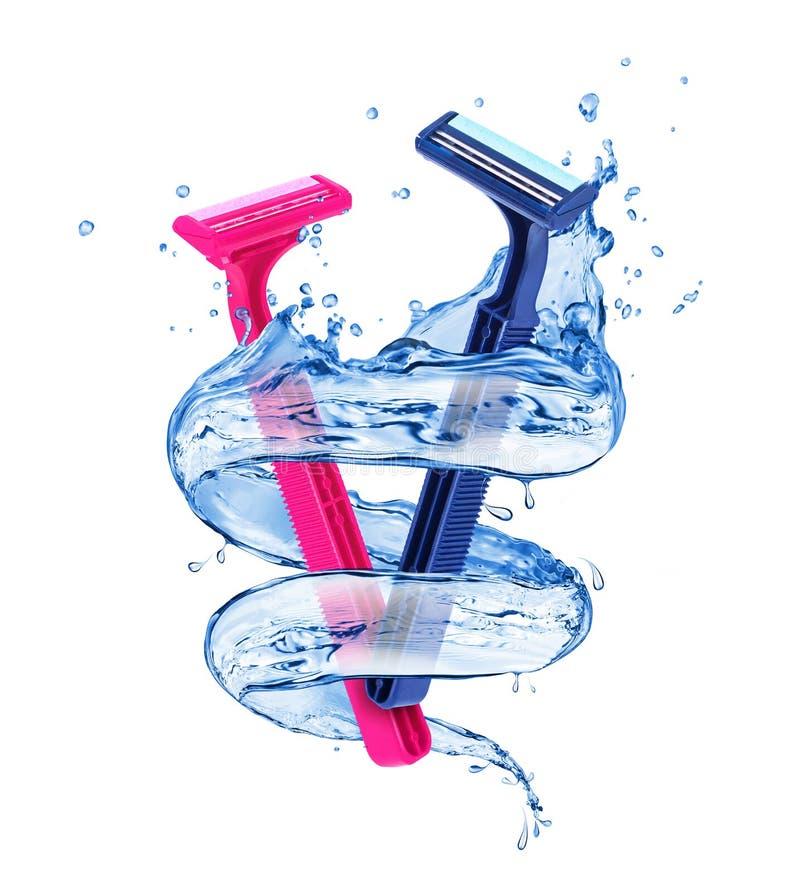 Roze damescheerapparaat en blauw scheerapparaat voor mensen met plonsen van water stock foto