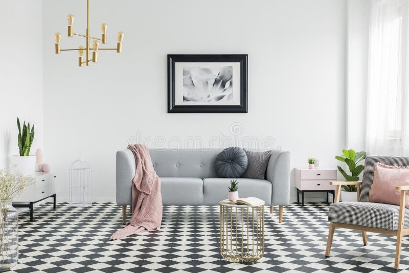 Roze deken en hoofdkussens op grijze laag in witte woonkamer inte royalty-vrije stock afbeeldingen
