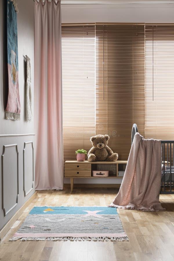 Roze deken op bed en deken in het heldere binnenland van de baby` s ruimte met stock foto