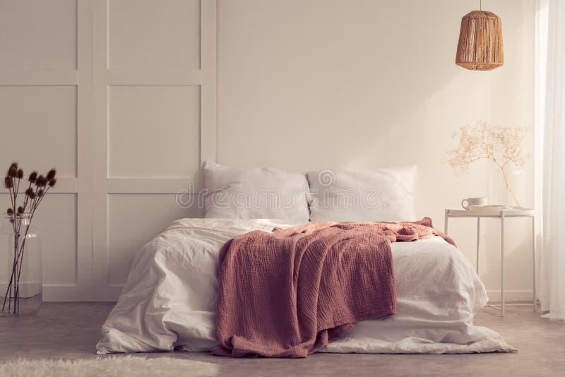 Roze deken op wit bed in minimaal slaapkamerbinnenland met lamp boven lijst met installatie stock afbeelding