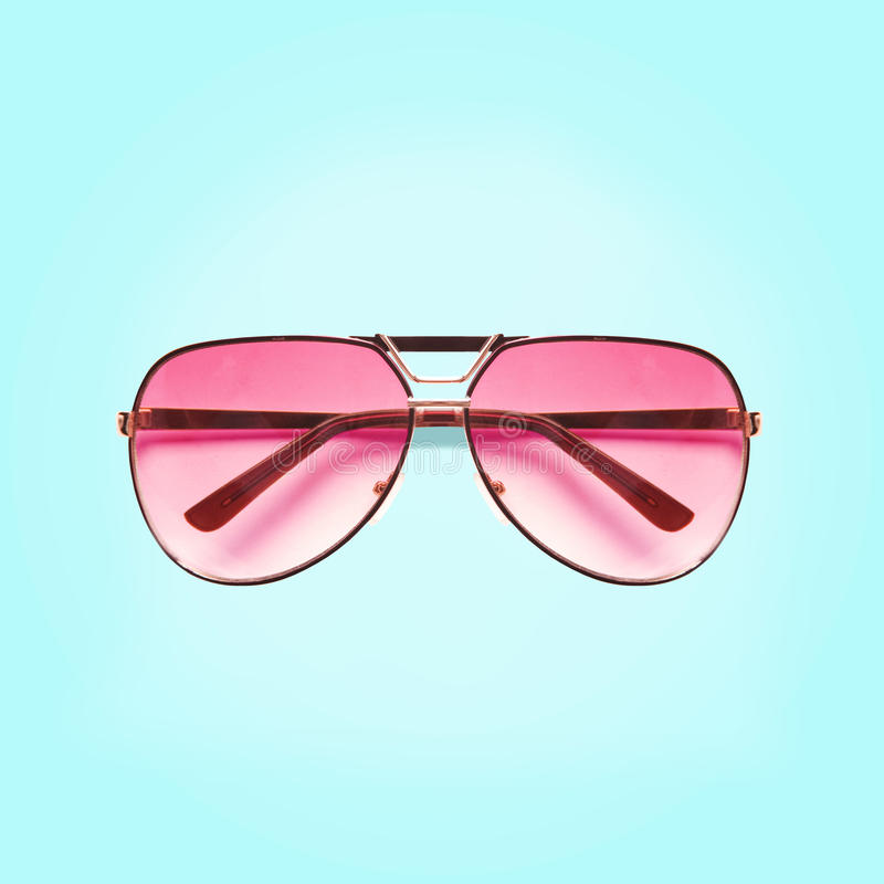 Roze die zonnebril op blauwe achtergrond wordt geïsoleerd stock afbeelding