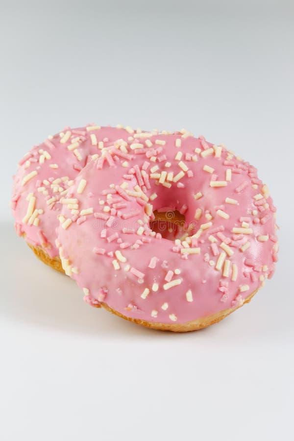 Roze donuts met sprincles op wit royalty-vrije stock afbeelding