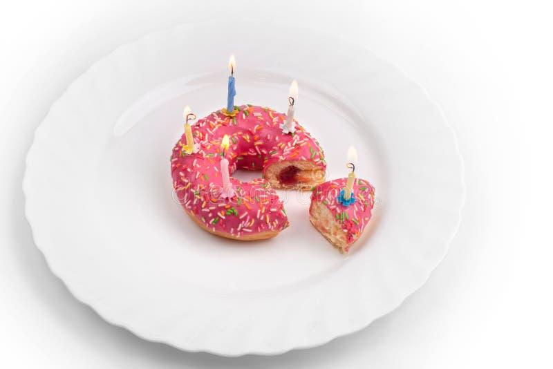 Roze doughnut op witte plaat zoals verjaardagscake met kaarsen op witte achtergrond royalty-vrije stock foto's