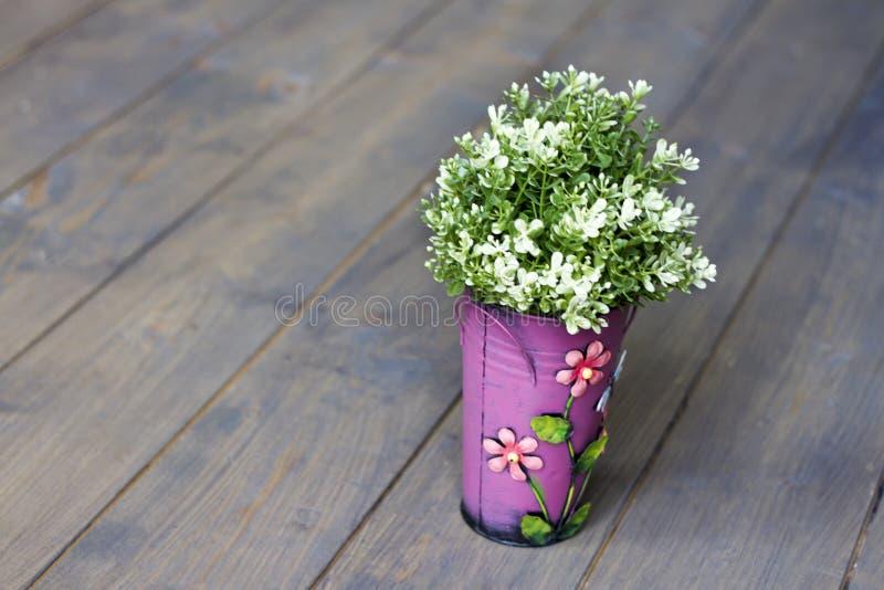 Roze emmer met bloemen Kunstmatige groene installatie Houten Vloer stock foto