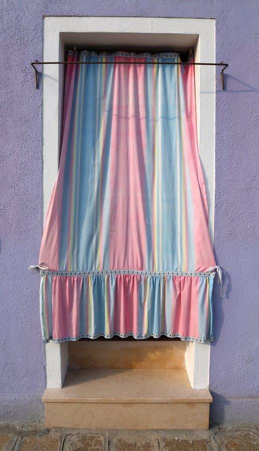 Roze en blauwe gordijnen voor de ingang van het huis stock foto's