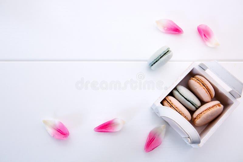 Roze en blauwe macaronkoekjes in de mand op witte achtergrond stock fotografie