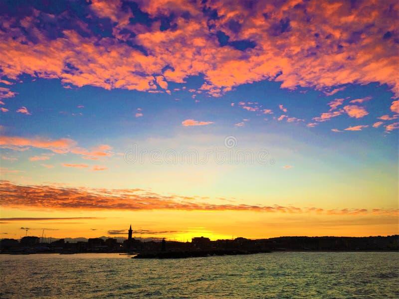Roze en gele zonsondergang, overzees en kleuren in de toeristische haven van Civitanova Marche royalty-vrije stock foto