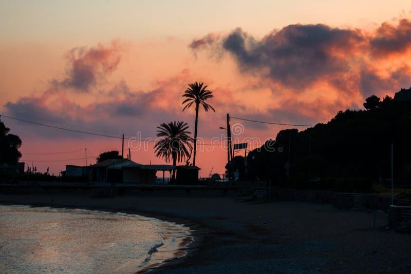 Roze en Gray Sky Looming Over de Strandkustlijn Nacht die beginnen te vallen Huizen en Bomen die tot een Silhouetvorm leiden royalty-vrije stock foto