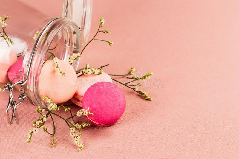 Roze en magenta Franse macarons of makarons, en uiterst kleine witte bloemen die van een glaskruik uitvallen die over een roze ta stock foto's