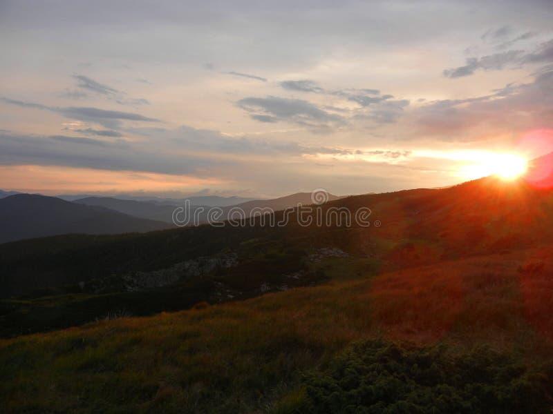 Roze en oranje zonsondergang in de bergen stock afbeeldingen
