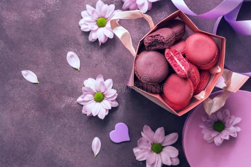 Roze en purper makaronclose-up in een giftdocument zak op een purpere die achtergrond met bloemen wordt verfraaid Hoogste mening, royalty-vrije stock afbeelding