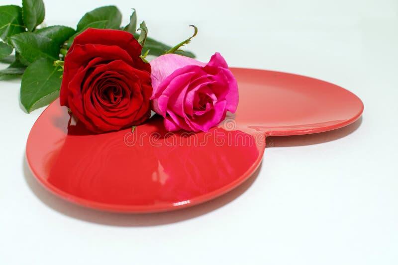 Roze en rood nam bovenop glanzende rode hart gevormde plaat toe royalty-vrije stock fotografie
