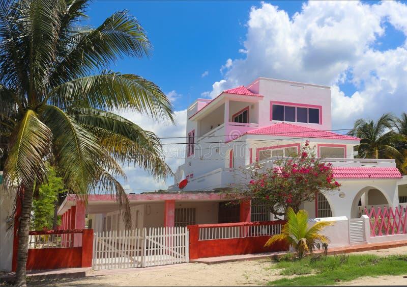 Roze en wit Mexicaans drie verhaalhuis met rode omheining en palm en bloeiende bomen tegen een mooie blauwe hemel met pluizige cl royalty-vrije stock foto's