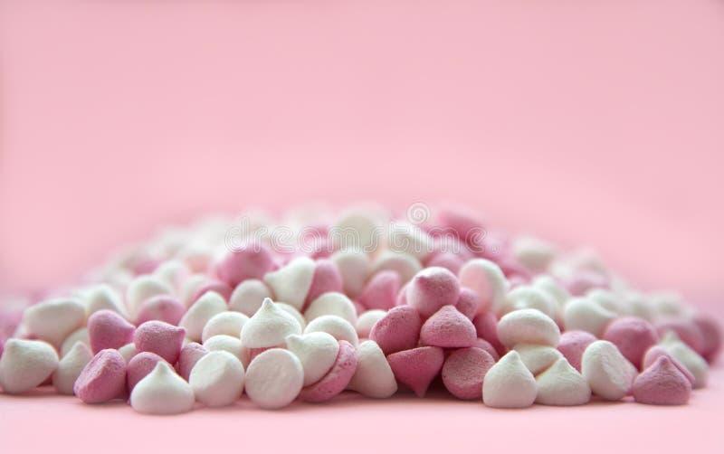 Roze en witte minischuimgebakjes in de vorm van dalingen, die op een roze achtergrond liggen Plaats voor tekst stock foto