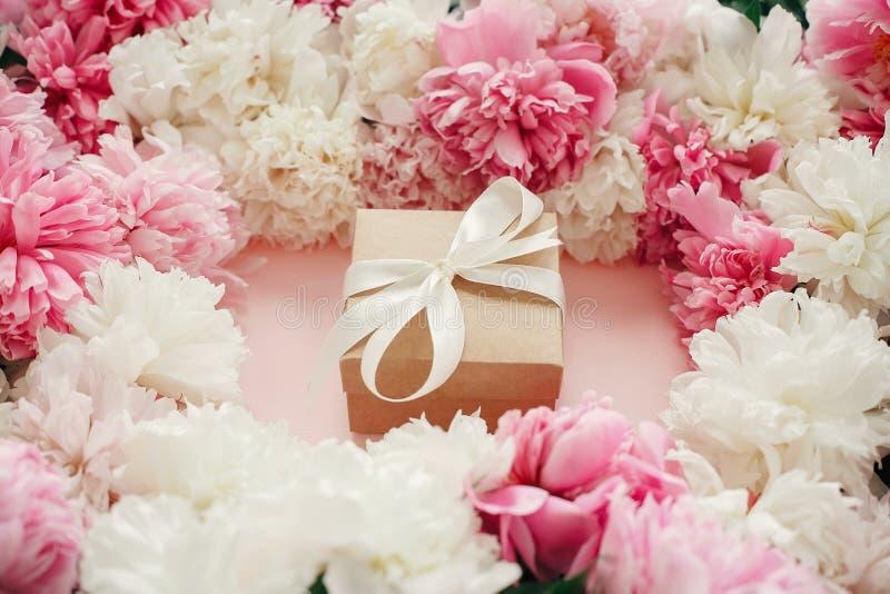 Roze en witte pioenen met giftvakje op pastelkleur roze document De ruimte van het exemplaar Gelukkige moedersdag, het bloemenmod stock afbeelding