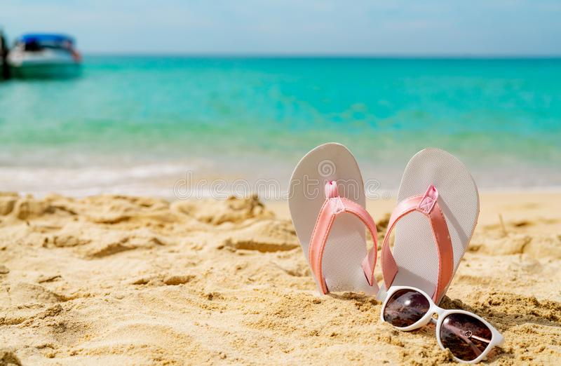 Roze en witte sandals, zonnebril op zandstrand bij kust De toevallige wipschakeling en de glazen van de manierstijl bij kust De z royalty-vrije stock fotografie