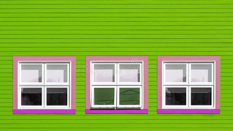Roze en witte vensters op kalk groene muur royalty-vrije stock foto