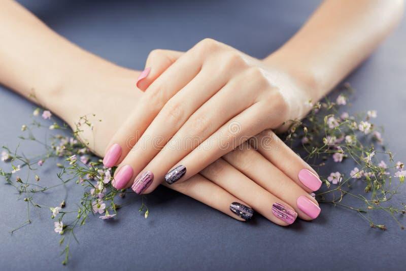 Roze en zwarte manicure met bloemen op grijze achtergrond Nagel art stock foto