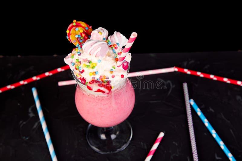Roze Extreme milkshake met rasberry bes, aardbei, suikergoedheemst royalty-vrije stock foto's