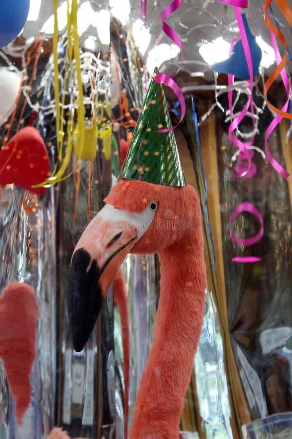 Roze flamingo met partijhoed in venster, wimpels en ballons die een verjaardag helpen te vieren stock foto's