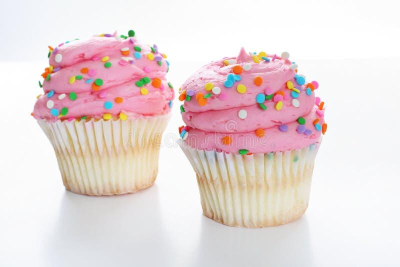 Roze gastronomische cupcake twee die op wit wordt geïsoleerdg royalty-vrije stock fotografie