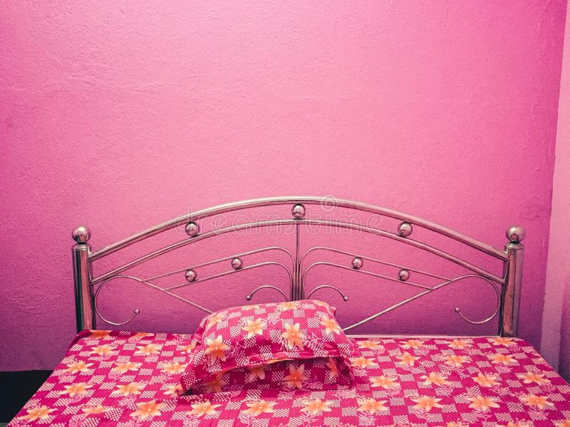 Roze gekleurd bed met bloemenbedblad met roze muren royalty-vrije stock fotografie