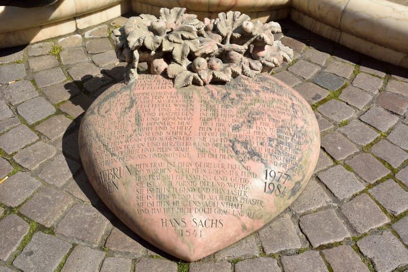 Roze-gekleurd hart-vormig beeldhouwwerk met Duitse inschrijvingen stock afbeelding