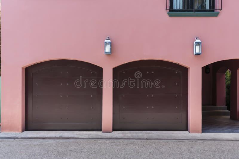 Roze gekleurd huis met twee autogarage stock foto